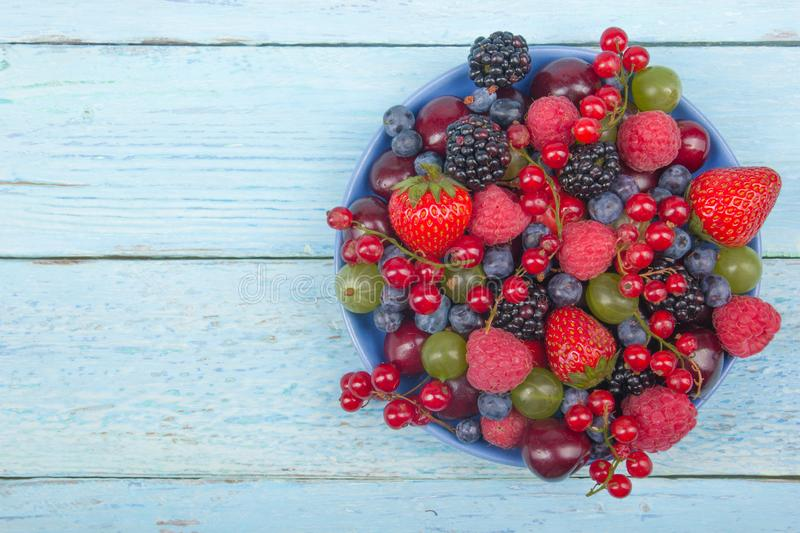 Various summer Fresh berries in a bowl on rustic wooden table. Antioxidants, detox diet, organic fruits. Top view royalty free stock photography