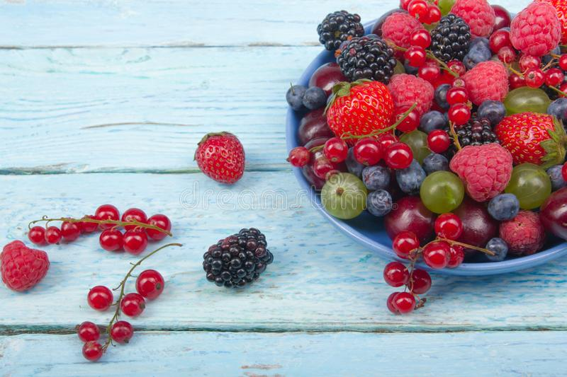 Various summer Fresh berries in a bowl on rustic wooden table. Antioxidants, detox diet, organic fruits. royalty free stock images