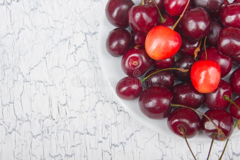 Various summer Fresh Cherry in a bowl on rustic wooden table. Antioxidants, detox diet, organic fruits. Top view royalty free stock photography