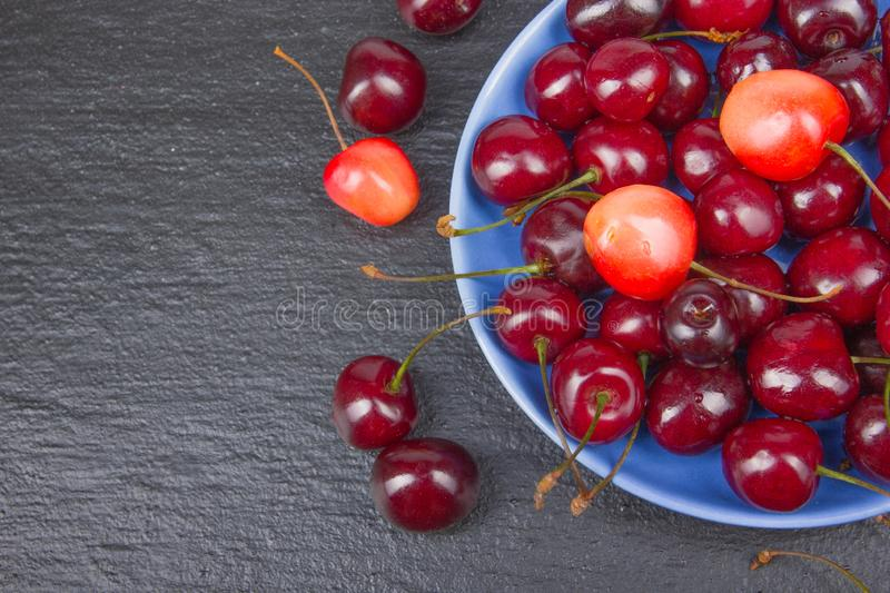Various summer Fresh Cherry in a bowl on rustic wooden table. Antioxidants, detox diet, organic fruits. Top view stock photo