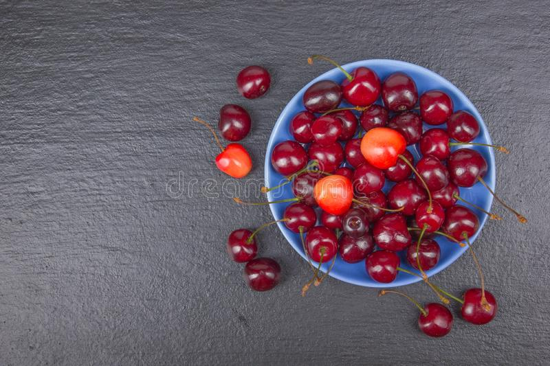 Various summer Fresh Cherry in a bowl on rustic wooden table. Antioxidants, detox diet, organic fruits. Top view stock photos