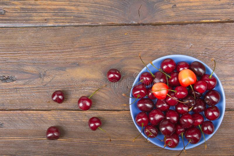 Various summer Fresh Cherry in a bowl on rustic wooden table. Antioxidants, detox diet, organic fruits. Top view royalty free stock images