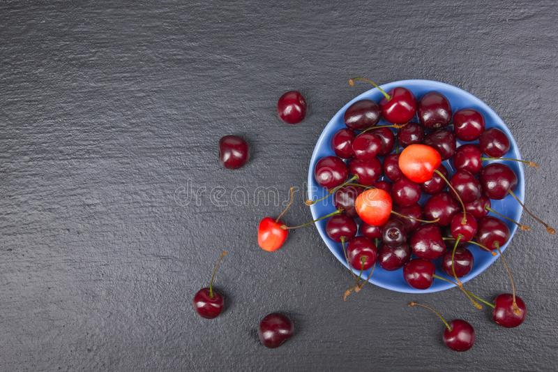 Various summer Fresh Cherry in a bowl on rustic wooden table. .Antioxidants, detox diet, organic fruits. Top view royalty free stock image