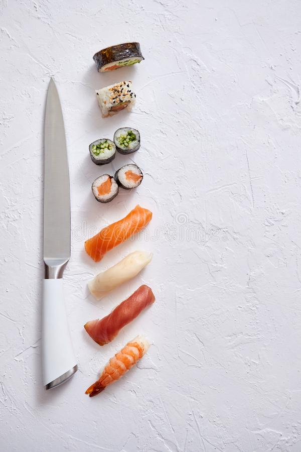 Various sushi rolls with Japanese knife on white stone slate background royalty free stock image