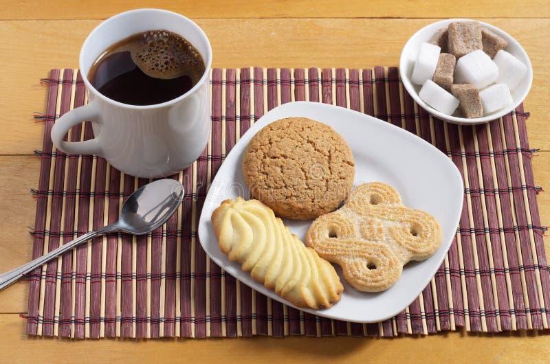 Various cookies, coffee and sugar cubes stock photos