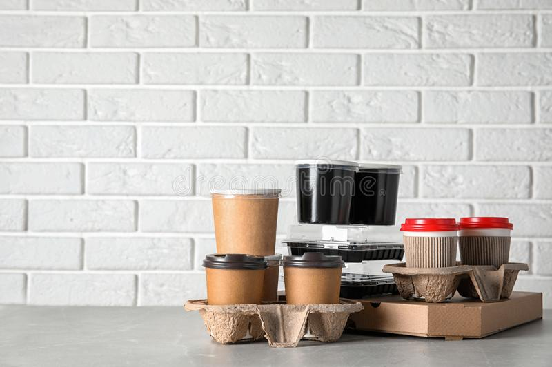 Various takeout containers on table against white brick wall, space for text. Food delivery service stock photography