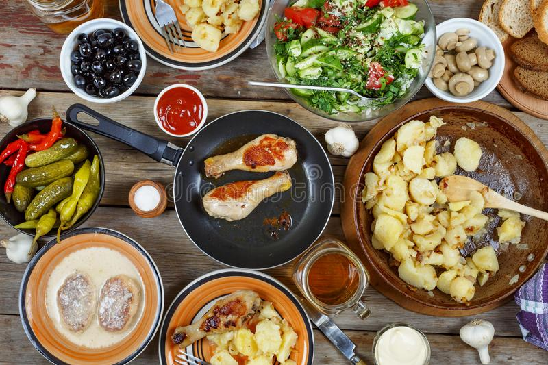 Various Traditional American snacks with grilled chicken legs and fried potatoes on the dining table. View from above. Concept of stock image