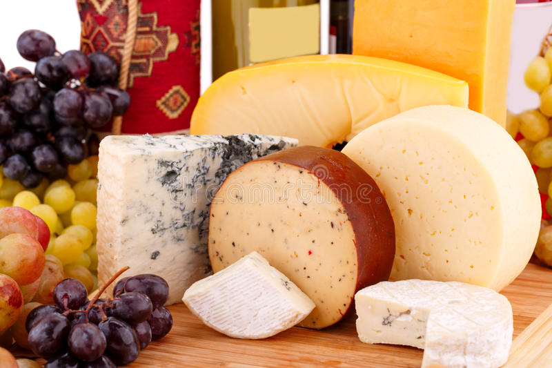 Various type of cheese. Wines and grapes on wooden board closeup picture royalty free stock images