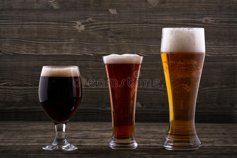 Various types of beer. On a wooden background royalty free stock photography