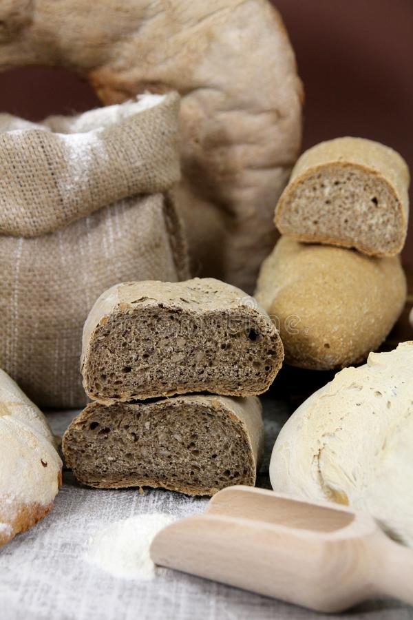 Various types of bread, white and whole grain bread loafs fresh. With flour on wooden table royalty free stock images