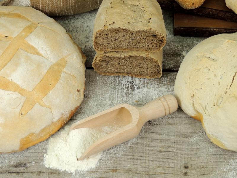 Various types of bread, white and whole grain bread loafs fresh. With flour on wooden table royalty free stock photography