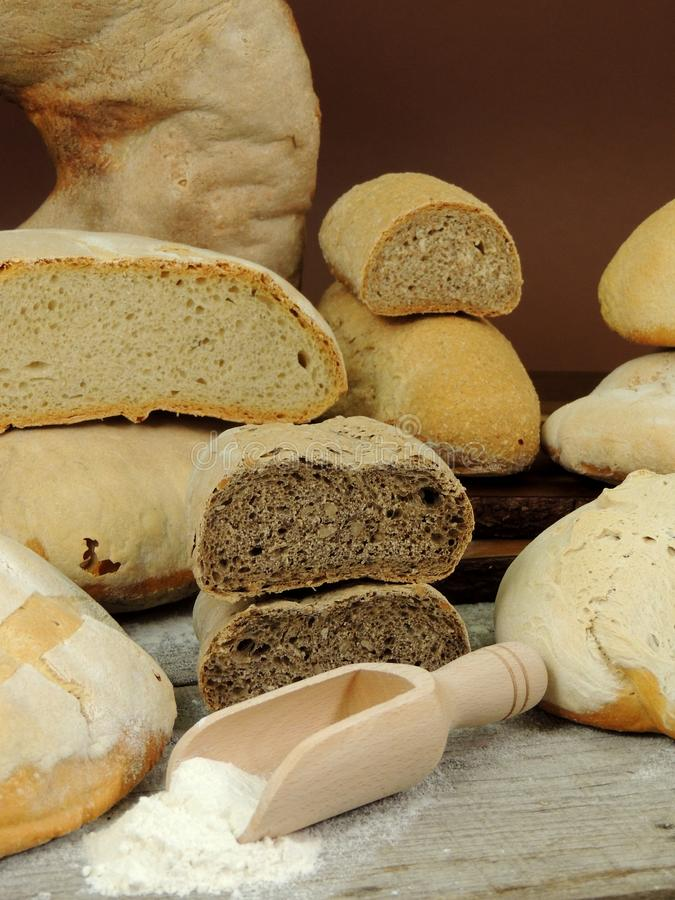 Various types of bread, white and whole grain bread loafs fresh. With flour on wooden table stock photos