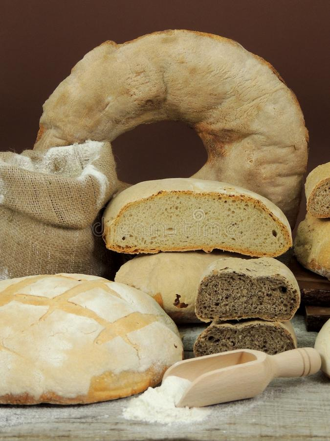 Various types of bread, white and whole grain bread loafs fresh. With flour on wooden table stock images