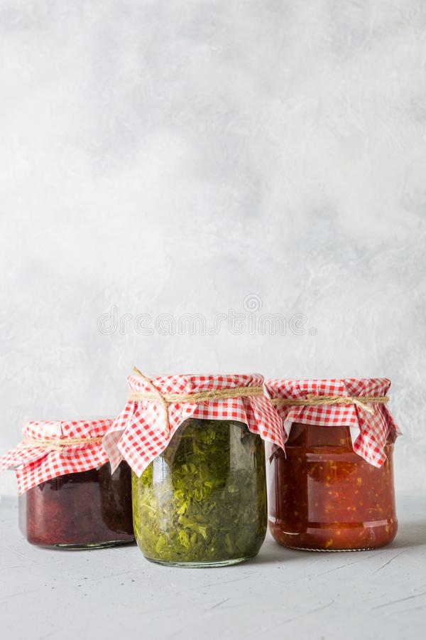 Various types of canned sauce for serving to meat, adjika from tomato, sorrel, tkemali from plum stock images