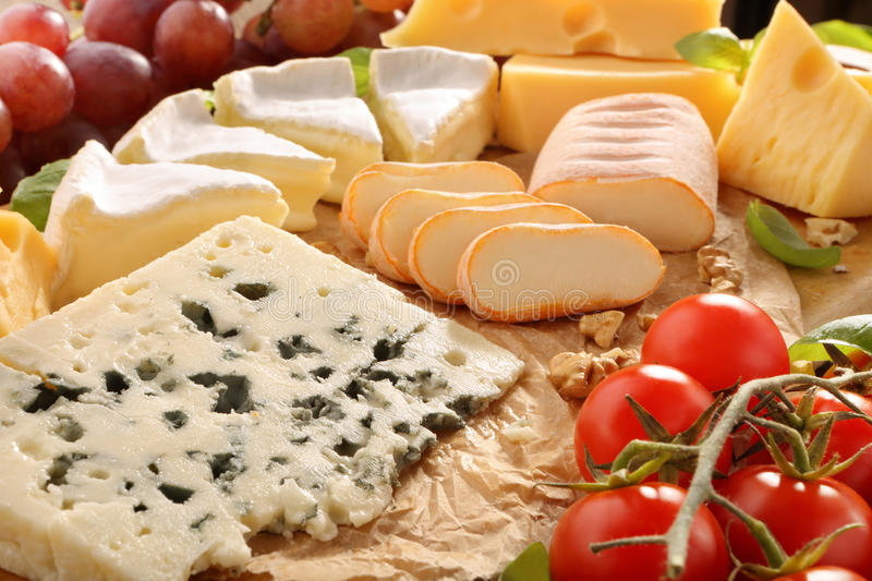 Various types of cheese board composition with tomato royalty free stock images