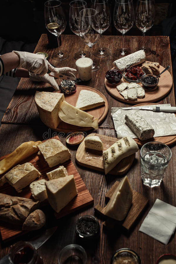 Various types of cheese with different spices and wine glasses on the empty space background stock photography