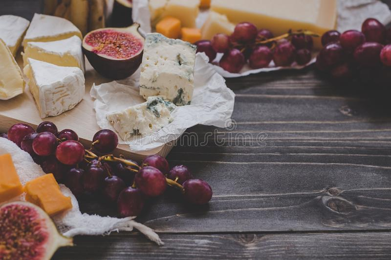 Various types of cheese with fruits and nuts on the wooden dark table. Selective focus stock photo