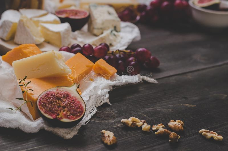 Various types of cheese with fruits and nuts on the wooden dark table. Selective focus stock photos