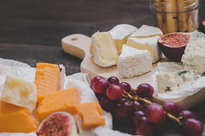 Various types of cheese with fruits and nuts on the wooden dark table. Selective focus stock images