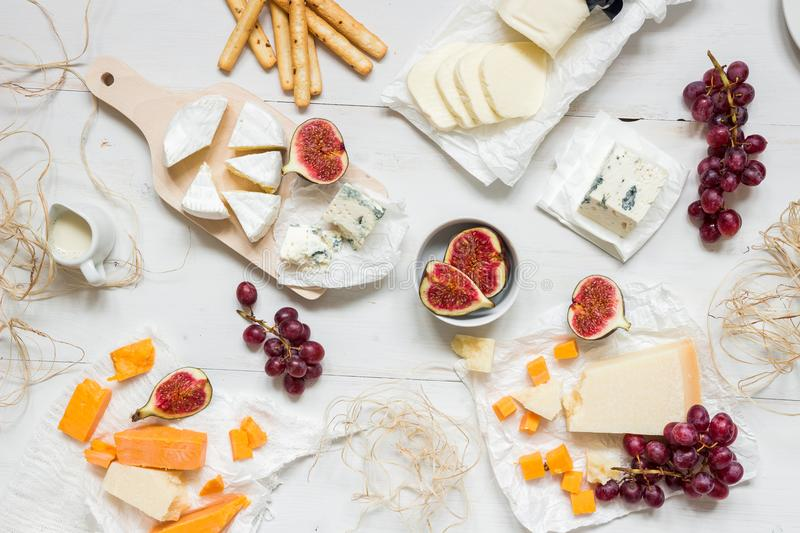 Various types of cheese with fruits and snacks on the wooden white table. Top view stock photo