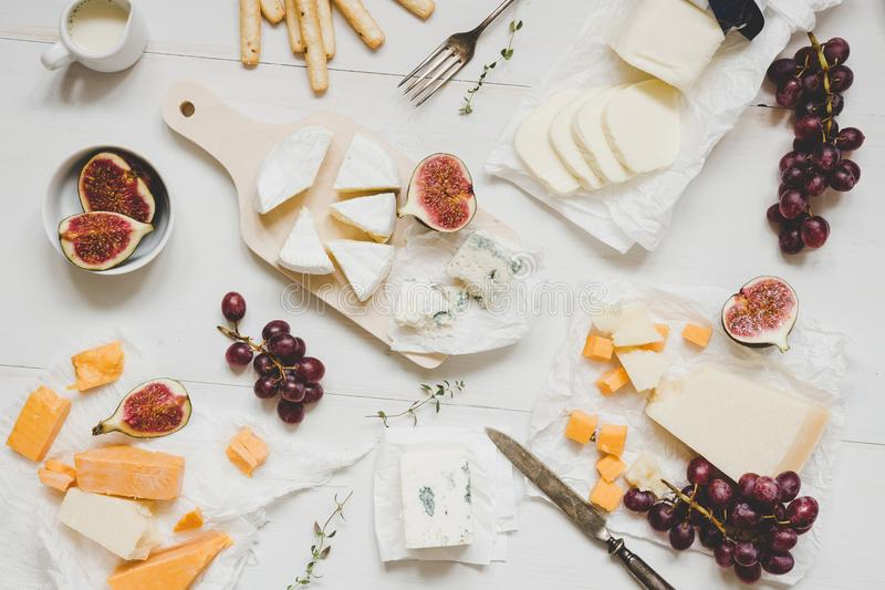 Various types of cheese with fruits and snacks on the wooden white table. Top view royalty free stock images