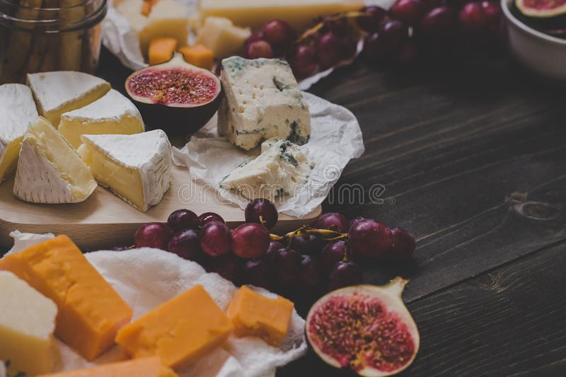 Various types of cheese with fruits on the wooden dark table. Selective focus royalty free stock photo