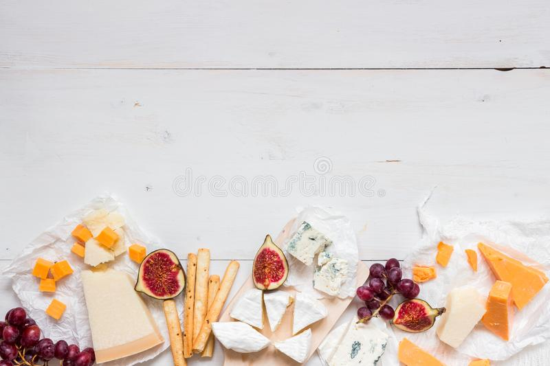 Various types of cheese with fruits on the wooden white table with copy space. Top view royalty free stock photo