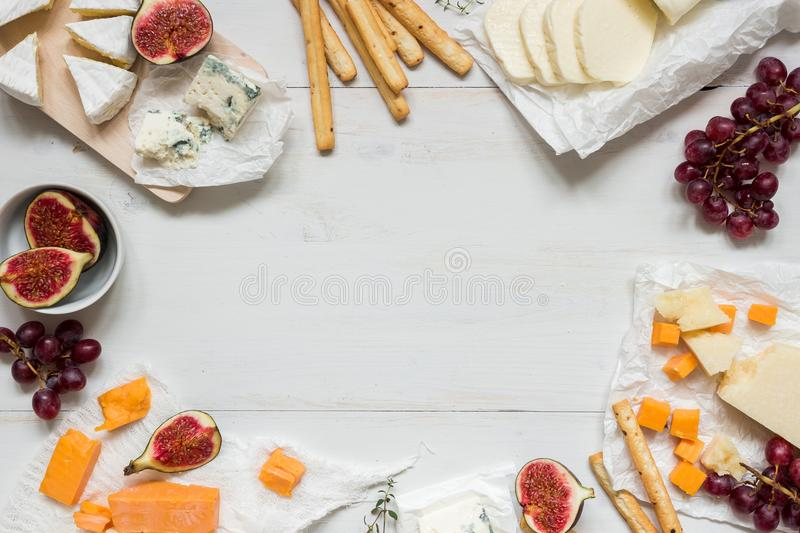 Various types of cheese with fruits on the wooden white table with copy space. Top view royalty free stock photos