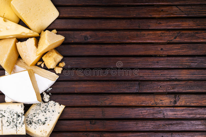 Various types of cheese on wooden table, top view stock images