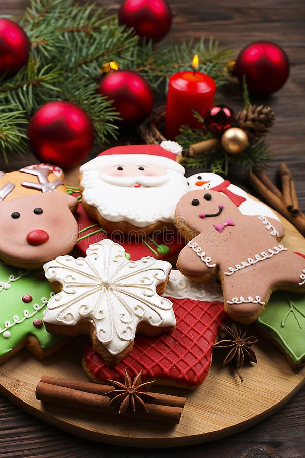 Various types of Christmas gingerbread cookies with fir tree branches, cinnamon sticks, anise star, candle and decoration close up stock photos