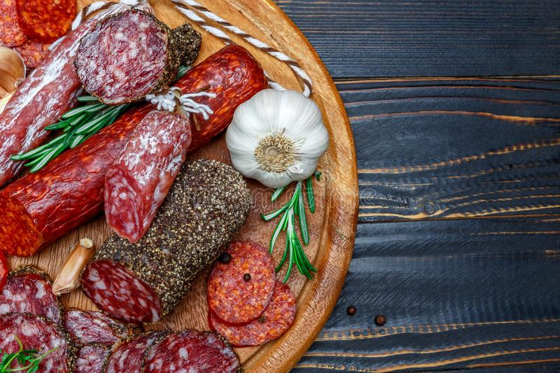 Various types of Dried organic salami sausage on wooden cutting board. Wooden background royalty free stock photos