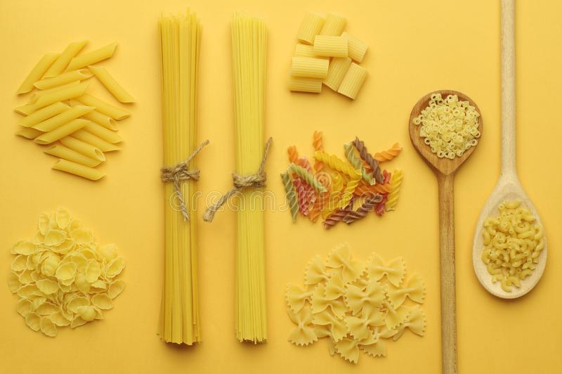 Various types of dry pasta : spaghetti, penne, farfalle, tagliatelle, fettuccine on a bright yellow background.Top view. royalty free stock photo
