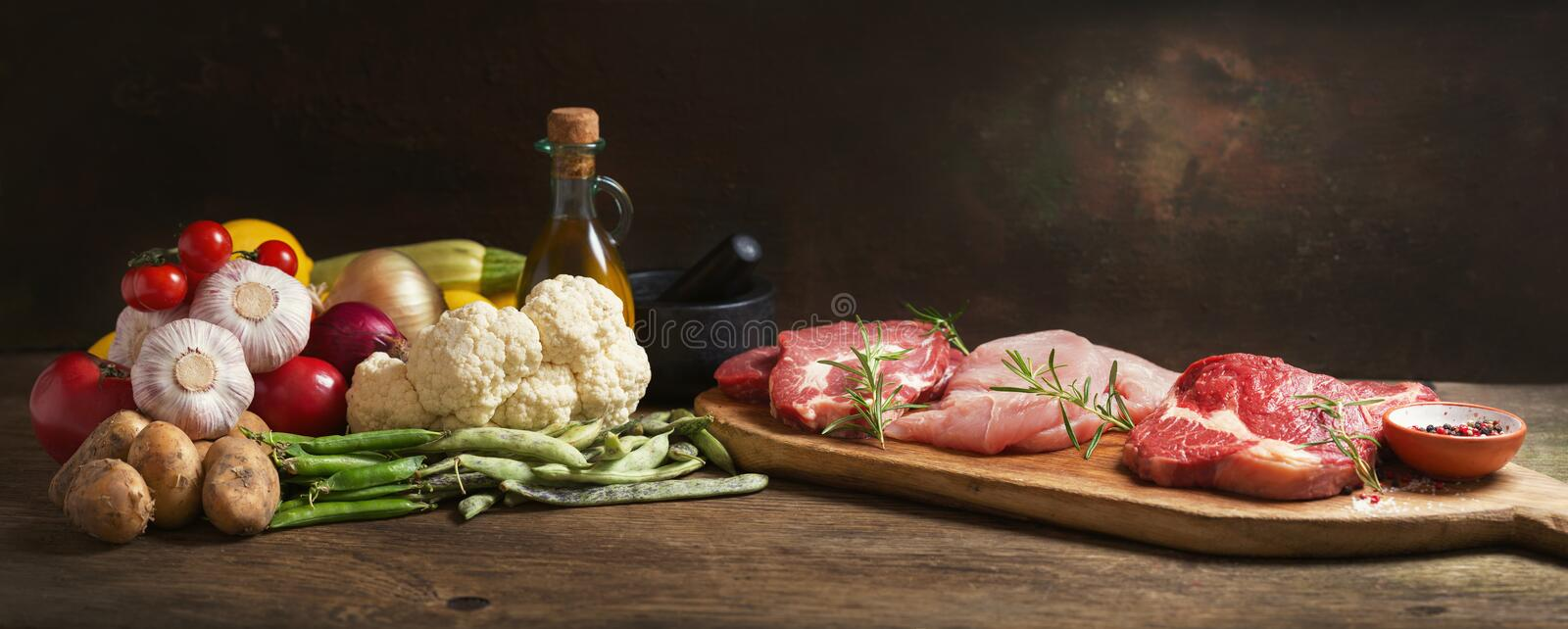 Various types of fresh meat steaks: beef, pork and turkey and ingredients for cooking stock images