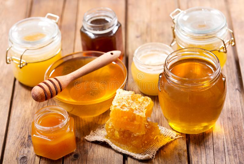 Various types of honey in glass jars stock images