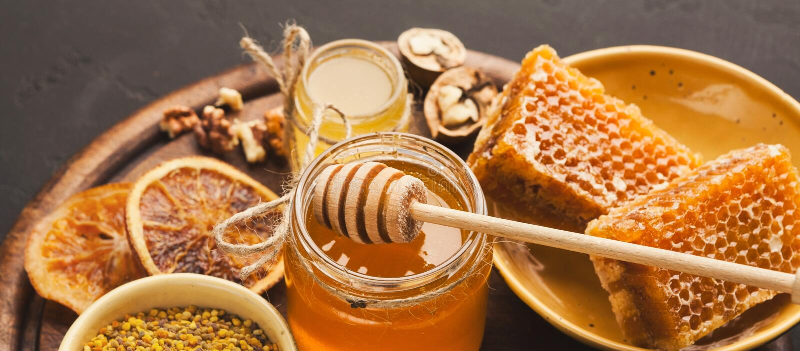 Various types of honey on wooden platter, closeup royalty free stock images