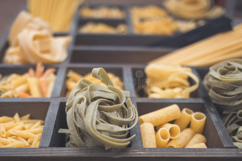 Various types of Italian pasta in a wooden box with different cells stock images