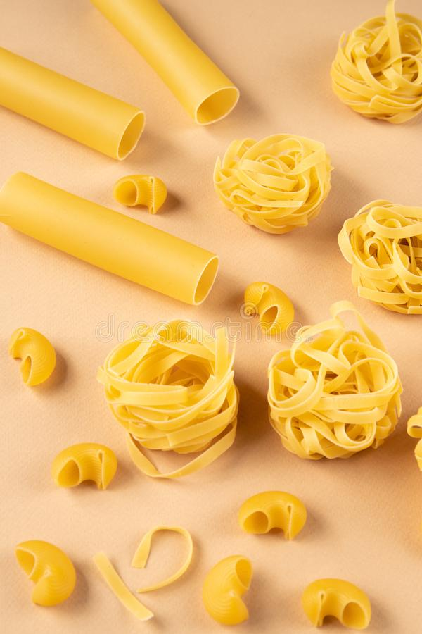 Various types of pasta on beige background. Different types of pasta on beige background. suitable for use in food industry stock photo