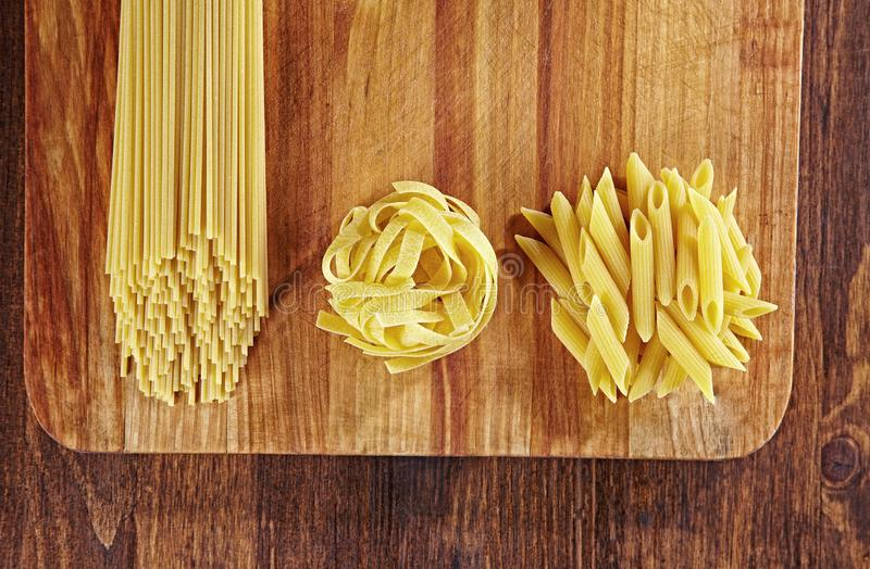 Various types of pasta on wooden table with cutting board, top view. Pappardelle, spaghetti, Penne pasta on dark wood royalty free stock image