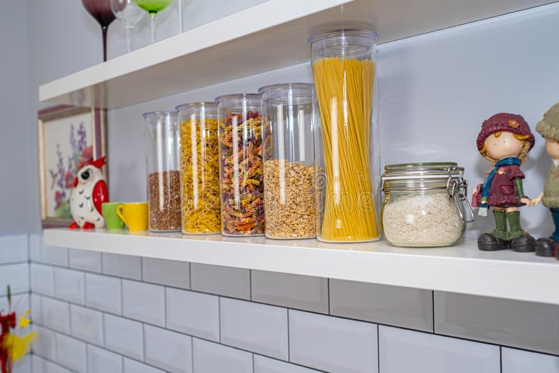 Various uncooked groceries in glass jars arranged on wooden shelves. Various uncooked groceries in glass jars arranged on wooden white shelves ar the kitchen royalty free stock images