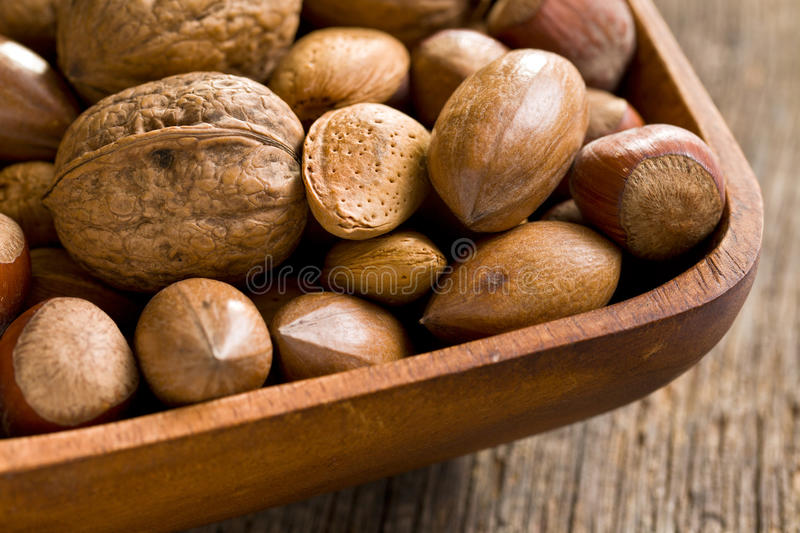 Various Unpeeled Nuts In Wooden Bowl Stock Photo