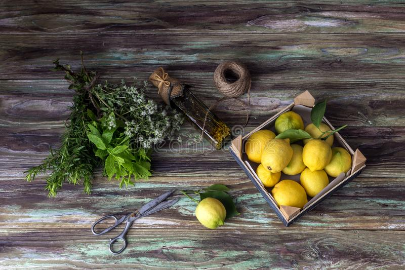Various herbs, spices, lemons and olive oil on a wooden background. Various useful herbs and spices. Mint, oregano, rosemary, lemons and olive oil in a bottle royalty free stock images