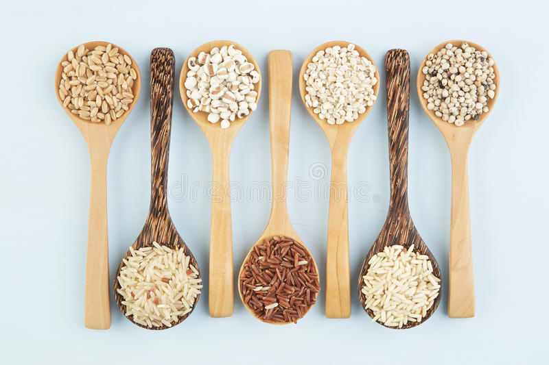 Various varieties of rice and wholegrains in spoon on wooden tab stock photography