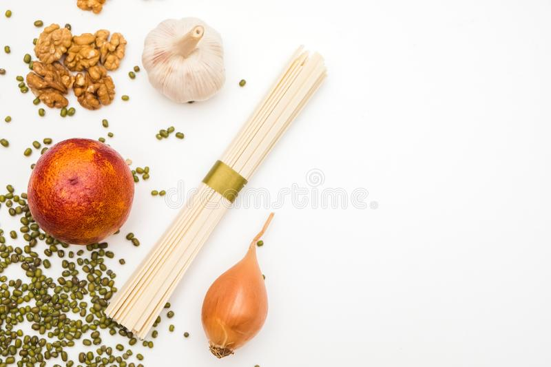 Various vegetables isolated on white background. Healthy food composition with noodles, garlic, orange, onion, walnut for pasta stock photography