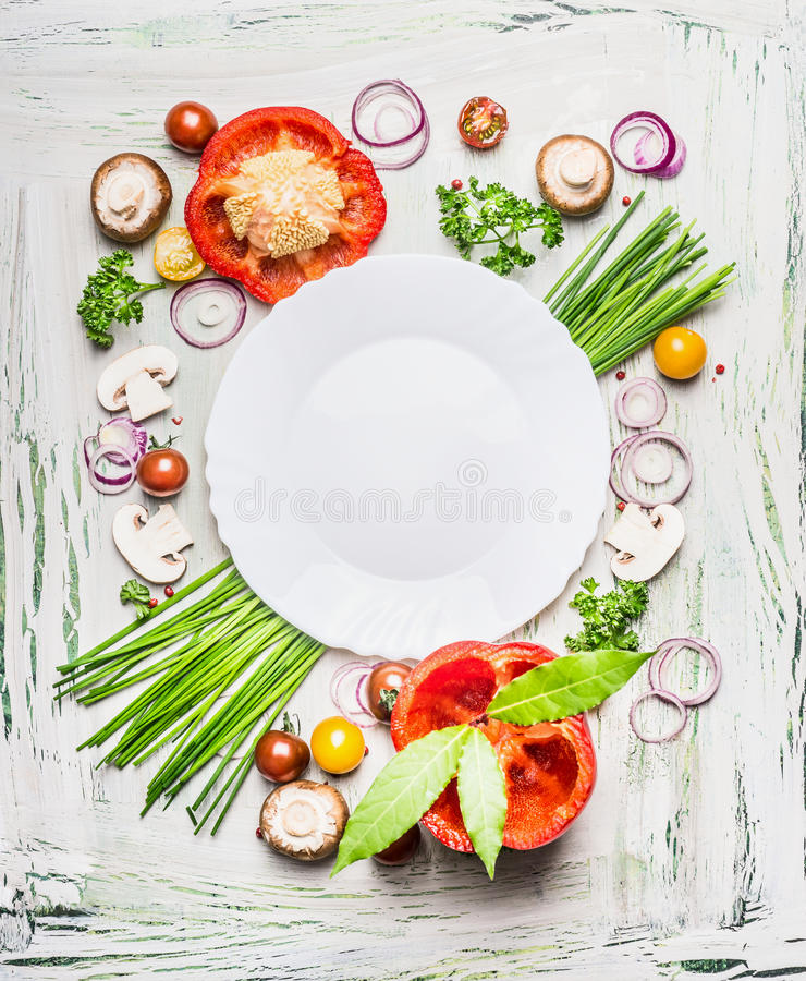 Various vegetables and seasoning cooking ingredients around blank plate on light rustic wooden background, top view composing royalty free stock photography