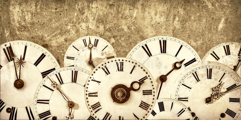 Various vintage clock faces in front of an old wall stock photography