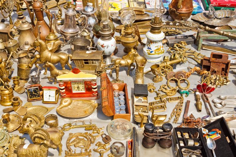 Various vintage things made of yellow metals for sale on a flea market royalty free stock photo