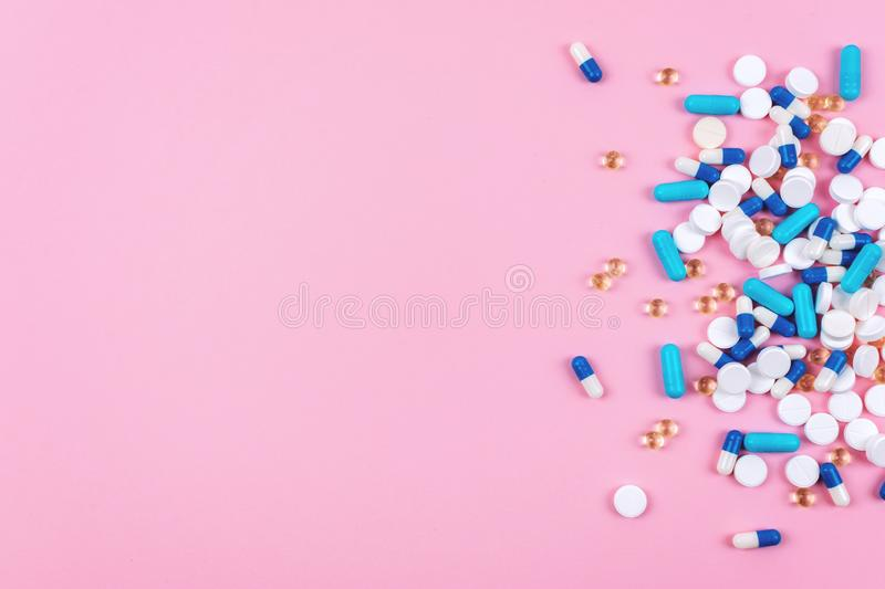 Various white and blue pills on pink background with copy space. Different medical drugs, tablets and pills. Flat lay, top view, royalty free stock photos