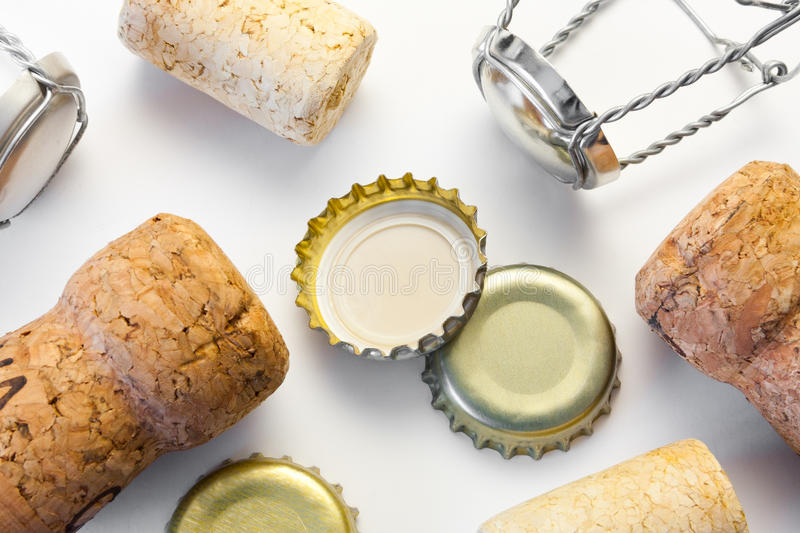 Various wine corks and bottle caps after party. Variety of wine bottle corks and beer bottle caps lying on white table surface after wild party with alcohol royalty free stock photography