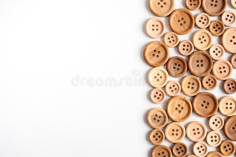 Various wooden beige buttons on a white background, flat lay stock photography