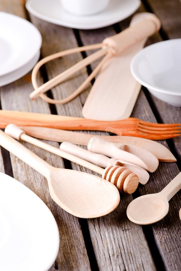 Various wooden spoons among white plates and bowls royalty free stock image